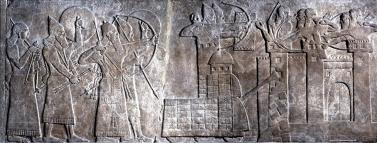 Rilievo che illustra l'assedio a una città fortificata e protetta da arcieri. Assurnasirpal (il terzo da sinistra) imbraccia un arco, vicino a lui si trovano un servitore e soldati protetti da scudi. Gli Assiri combattono usando una torre di legno, sulla cui sommità si trovano degli arcieri, e un ariete che sta distruggendo le mura della città. © The Trustees of the British Museum