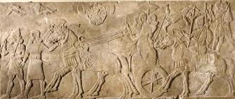 Assurnasirpal torna vittorioso dalla guerra. Il re è in piedi sul carro, un servitore lo ripara con un ombrello. Soldati a piedi e a cavallo partecipano al corteo. In alto si vedono i corpi dei nemici sconfitti e al centro una divinità alata. © The Trustees of the British Museum