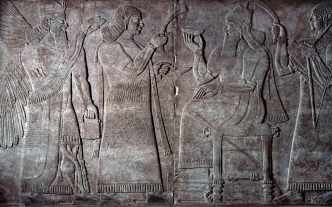 Questo rilievo mostra una scena di corte. Assurnasirpal è seduto sul trono circondato da due servitore. A sinistra c'è uno spirito protettore alato. © The Trustees of the British Museum